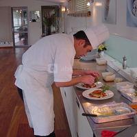 Le chef concocte un repas devant le client